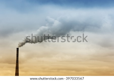 Heavy industrial smoke erupts from factory's chimney into the sky with blue and yelllow colors - stock photo