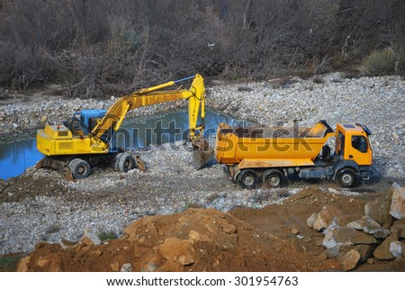 Heavy machinery for construction and public works. Excavator and truck - stock photo