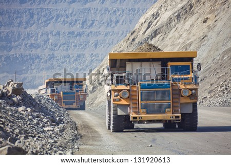 Heavy mining dump trucks driving along the opencast - stock photo