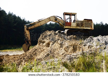 heavy, old and broken orange excavator / digger with shovel standing on hill with rocks - stock photo