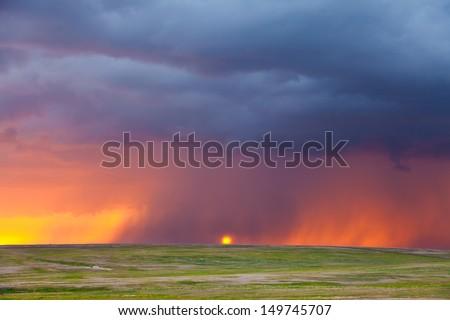 Heavy rain at sunset - stock photo
