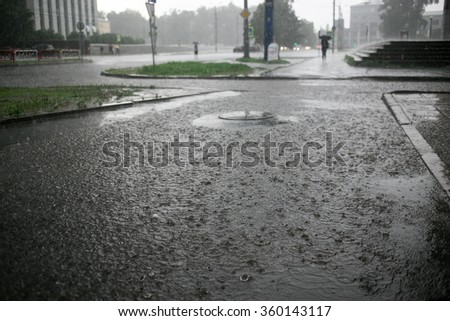 heavy rain drops falling on city street during downpour - stock photo