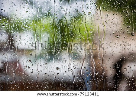 heavy rain drops on window with green background - stock photo
