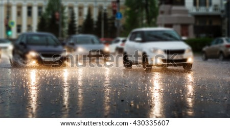 Heavy rain hitting a concrete sidewalk while cars drive by. Selective focus. - stock photo