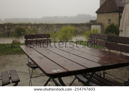 heavy rain on a outside restaurant table - stock photo
