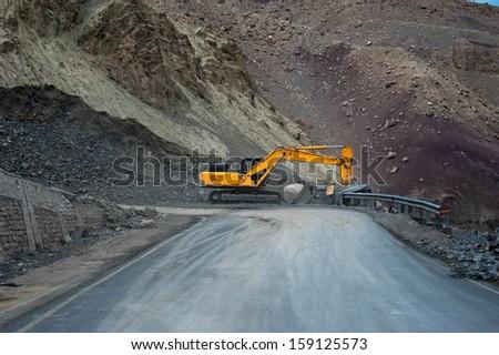 Heavy road construction car in Himalaya mountains. India, Ladakh, altitude 4500 m - stock photo