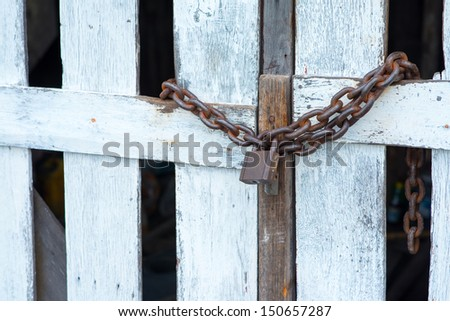 Heavy rusty chains and padlocks on a fragile wooden door. - stock photo