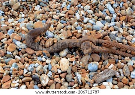 Heavy rusty hook and cable lying on a shingle beach - stock photo
