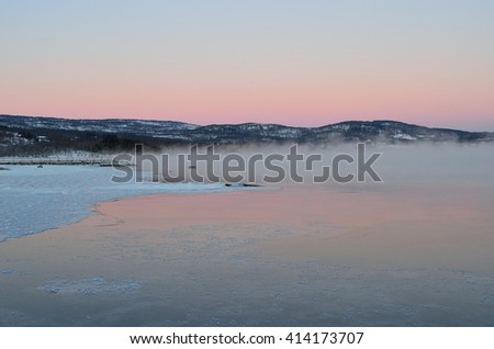 heavy sea ice fog over fjord landscape with dense ice fog and vibrant colorful dawn sky - stock photo