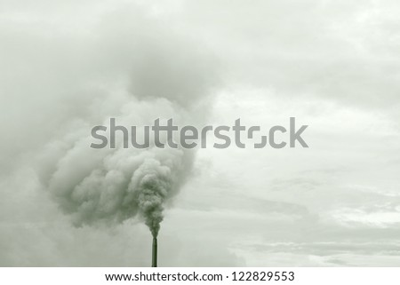 Heavy smoke billowing from an industrial chimney against a cloudy sky. - stock photo