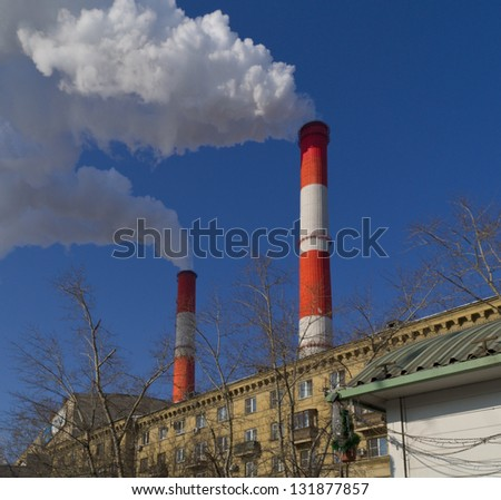 heavy smoke from couple red pipe on blue sky background. - stock photo