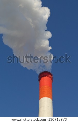 heavy smoke from red pipe on blue sky background. - stock photo