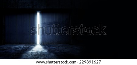 Heavy steel doors opening. Large steel doors of an hanger like building opening and light coming in. with copyspace - stock photo