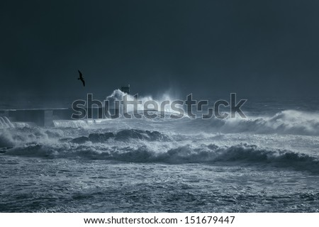 Heavy storm at the entrance of the Douro river harbor. The light is coming from a momentary sunbeam. Toned blue. - stock photo
