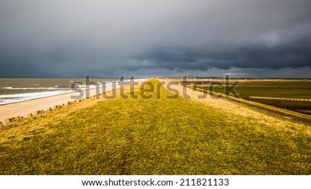 Heavy Storm Clouds over a Dutch dike near the sea - stock photo