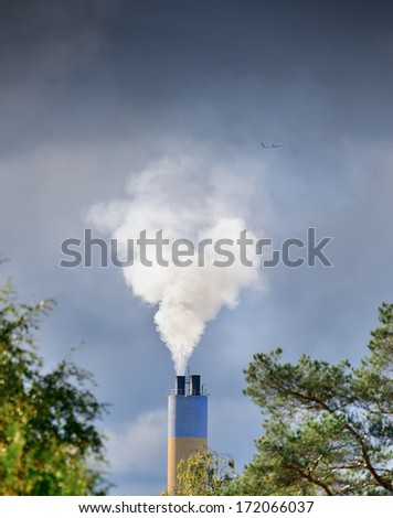 Heavy sunlit smoke and chimney. Airplane in the background. - stock photo