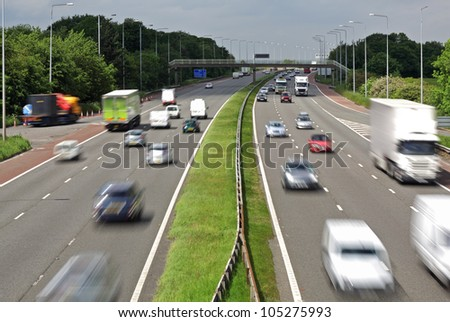 Heavy traffic moving at speed on the M6 motorway in England - stock photo