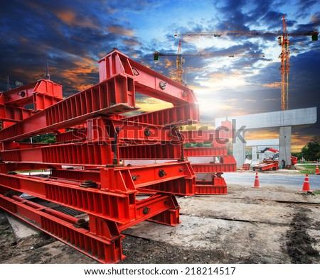heavy trains bridge crossing highways in construction with part of big crane structure on ground - stock photo