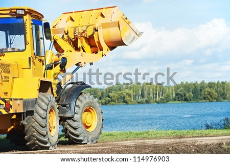 heavy wheel loader excavator machine loading sand at quarry - stock photo