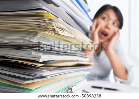 Heavy workload concept with surprised woman on background. Selective focus - stock photo