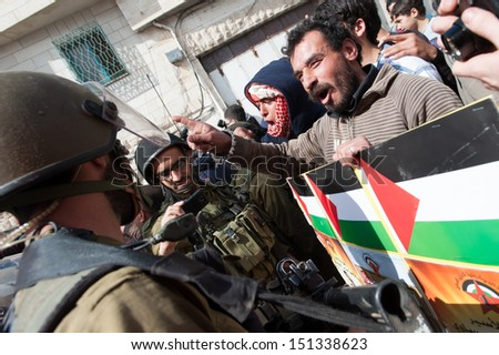 HEBRON, PALESTINIAN TERRITORY - MARCH 1: Palestinian activists confront Israeli soldiers during a demonstration against the occupation in the West Bank city of Hebron, March 1, 2013. - stock photo
