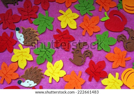 Hedgehog, squirrel and leaves out of felt on a pink fabric as a background - stock photo