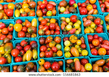 Heirloom small tomatoes on display at the farmers market - stock photo