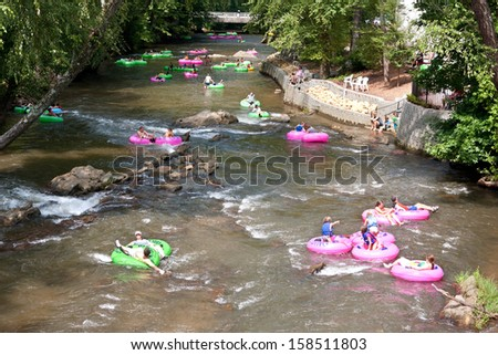 HELEN, GA - AUGUST 24:  People enjoy tubing down the Chattahoochee River in North Georgia on a warm summer afternoon, on August 24, 2013 in Helen, GA.  Hundreds of people went tubing down the river. - stock photo