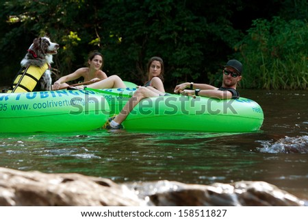 HELEN, GA - AUGUST 24:  People tube down the Chattahoochee River in North Georgia, with a dog wearing a life vest in its own tube, on August 24, 2013 in Helen, GA.  Hundreds went tubing on the river. - stock photo