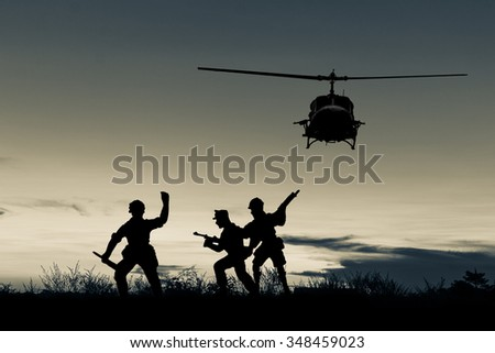 helicopter and soldier silhouette multicolored sunset photo as background - stock photo