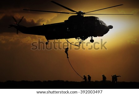Helicopter dropping soldier during sunset - stock photo