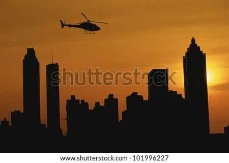 Helicopter flying over Atlanta skyline at sunset - stock photo