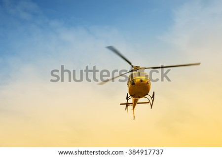 Helicopter in flight at sunset in summer - stock photo