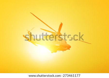 helicopter in the sky at sunset - stock photo