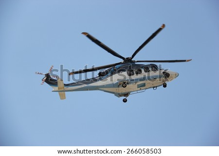 Helicopter is flying in bright blue sky. - stock photo