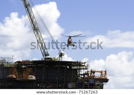 Helicopter landing on offshore oil rig. - stock photo