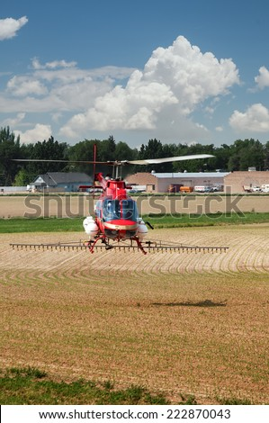 Helicopter used to spread liquid fertilizer on a farm field. - stock photo