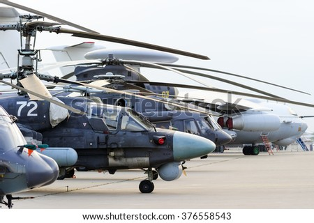 Helicopters and planes in row, military copters and bomber jets and reconnaissance aircrafts, air force, modern army aviation and aerospace industry  - stock photo