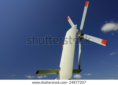 Helicopters tail blades against deep blue sky - stock photo