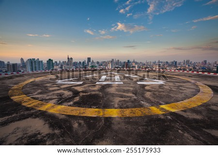 Helipad on the roof of a skyscraper with cityscape view - stock photo