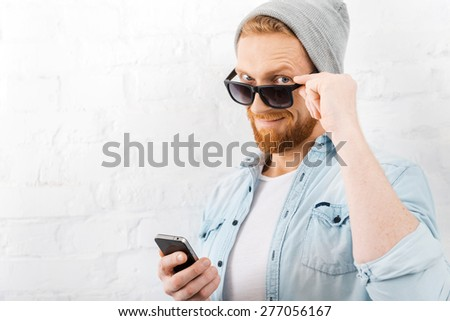 Hello! Confident young bearded man adjusting his eyewear and holding mobile phone while standing against brick wall - stock photo