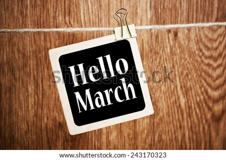 Hello March text written on a chalkboard with a wood wall background - stock photo