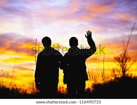 Hello. Two men stand in the background of a beautiful sunset and waving his hand in greeting Hello. Silhouettes in the contre. Special light. - stock photo