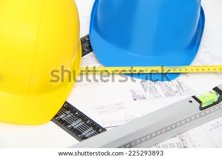 Helmets and tools for construction drawings and buildings - stock photo