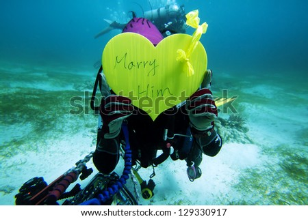 Help friend to propose in underwater - stock photo