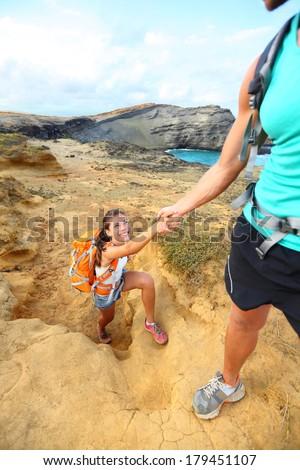 Help - hiker woman getting helping hand hiking on hike smiling happy. Tourist backpackers walking on Green Sand Beach, Papakolea on Big Island, Hawaii, USA. Young couple traveling with backpacks. - stock photo