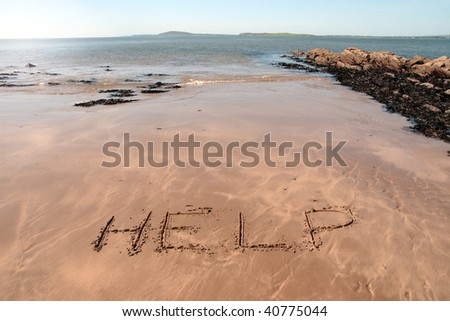 help inscribed on the beach with waves in the background on a hot sunny day - stock photo