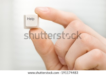 Help. Man's hand holding computer key on white background. - stock photo