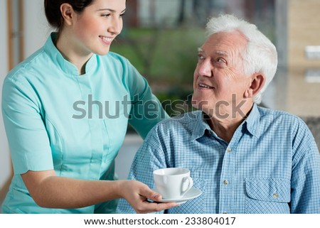 Helper giving senior man cup of coffee - stock photo