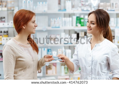 Helpful advice. Attractive smiling pharmacist giving her client pills at the local drug store. - stock photo